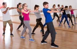 Grupp av positiva le tonåringar som dansar i klassrum royaltyfri bild