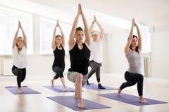 Grupp av praktiserande yoga för ungt sportigt folk som gör krigare en royaltyfri bild