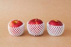 Grupp av röda äpplen med skyddande förpacka på pappers- bakgrunder Royaltyfria Foton