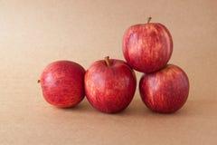 Grupp av röda äpplen på bakgrund för brunt papper Arkivbilder