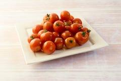 Grupp av röda mini- tomater på en platta Arkivfoto