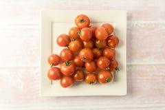 Grupp av röda mini- tomater på en platta Arkivbilder