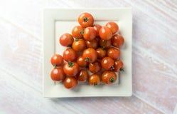 Grupp av röda mini- tomater på en platta Royaltyfri Foto