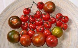 Grupp av röda tomater på den vita plattan Fotografering för Bildbyråer