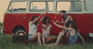 Grupp av retro stilfulla vänner som tillsammans spenderar en stor tid på natursammanträdet bak den retro skåpbilen och spela lager videofilmer