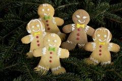 Grupp av roliga pepparkakapojkar och flickor på julträd royaltyfri fotografi