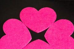 Grupp av rosa hjärtor mot en mörk bakgrund. Arkivfoton