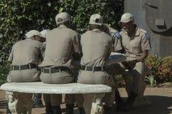 Grupp av söder - afrikanskt sammanträde för trafikpolisen på en tabell Arkivfoto