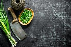 Grupp av salladslöken med den högg av salladslöken på en platta, gammal kniv och att tvinna royaltyfri fotografi