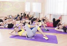 Grupp av sju kvinnliga idrottsman nen som utför Fitnes övningar Royaltyfri Foto