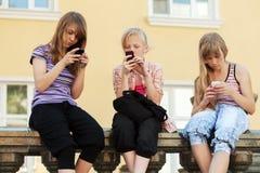 Grupp av skolaflickor som kallar på telefonerna Royaltyfria Bilder