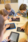 Grupp av skolaungar med minnestavlaPC i klassrum Arkivbild