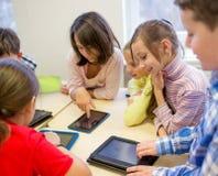Grupp av skolaungar med minnestavlaPC i klassrum Fotografering för Bildbyråer