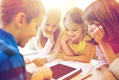 Grupp av skolaungar med minnestavlaPC i klassrum Arkivfoton
