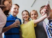 Grupp av skolaungar med smartphone- och sodavattencanen Royaltyfri Foto