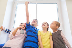 Grupp av skolaungar med smartphone- och sodavattencanen Royaltyfria Foton
