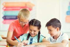 Grupp av skolbarn som lär på klassroom i skola royaltyfri foto