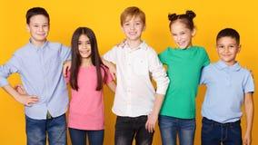 Grupp av skolbarn som står i rad som ser kameran fotografering för bildbyråer
