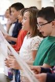 Grupp av skolbarn som tillsammans sjunger i kör fotografering för bildbyråer