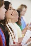 Grupp av skolbarn som tillsammans sjunger i kör Arkivfoto