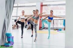 Grupp av slanka Caucasian flickor som står i en-ben slagställning under genomköraregrupp i idrottshall royaltyfri fotografi