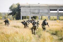 Grupp av soldater som är förlovade i utforskningområdet Arkivfoto
