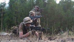 Grupp av soldater som siktar med vapen lager videofilmer