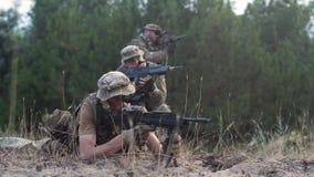 Grupp av soldater som siktar med vapen fotografering för bildbyråer