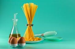 Grupp av spagetti som står som är upprätt på en ljus kulör bakgrund som omges, genom fegt ägg, olivolja och att laga mat royaltyfria bilder