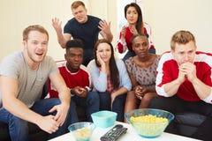 Grupp av sportfans som hemma håller ögonen på leken på TV arkivfoto