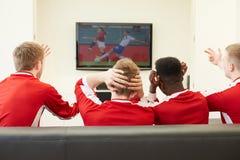 Grupp av sportfans som hemma håller ögonen på leken på TV Arkivfoton