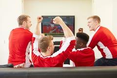 Grupp av sportfans som hemma håller ögonen på leken på TV Fotografering för Bildbyråer