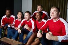 Grupp av sportfans som hemma håller ögonen på leken på TV Royaltyfri Bild