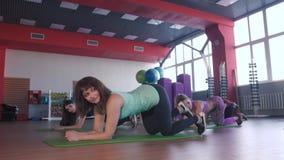 Grupp av Sportive folk i en idrottshallutbildning utför övningar på musklerna av benen arkivfilmer