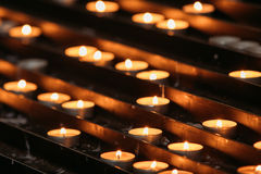 Grupp av stearinljus i kyrka Stearinljus ljus bakgrund Fotografering för Bildbyråer