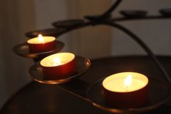Grupp av stearinljus p? m?rk bakgrund i en kyrka arkivfoto