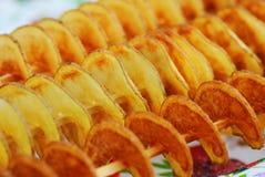 Grupp av stekte spirala potatissteknålar Stekte spirala skivapotatissteknålar Arkivfoto