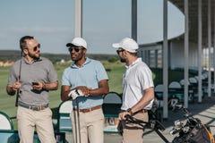 Grupp av stilfulla golfspelare som talar för lek Royaltyfria Foton