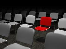 Grupp av stolar med en röd stol som ut står Fotografering för Bildbyråer