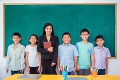 Grupp av student- och lärareanseende i klassrum arkivfoto