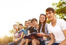 Grupp av studenter eller tonåringar med anteckningsböcker utomhus royaltyfria foton