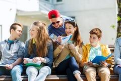 Grupp av studenter med anteckningsböcker på skolgården fotografering för bildbyråer