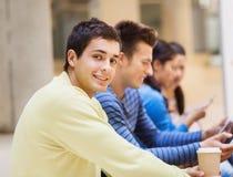 Grupp av studenter med minnestavlaPC och kaffekoppen Arkivbild
