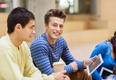 Grupp av studenter med minnestavlaPC och kaffekoppen Arkivfoto