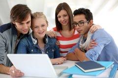 Grupp av studenter som använder bärbara datorn på skolan arkivfoto