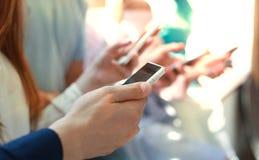 Grupp av studenter som håller ögonen på smartphones Ungdomarböjelse till ny tekniktrender fotografering för bildbyråer