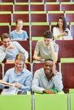 Grupp av studenter som har gyckel i föreläsning royaltyfri foto