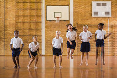 Grupp av studenter som hoppar i skolaidrottshall arkivbilder