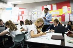 Grupp av studenter som lär i klassrum arkivfoton