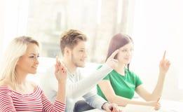 Grupp av studenter som lyfter händer i ett klassrum Arkivbild